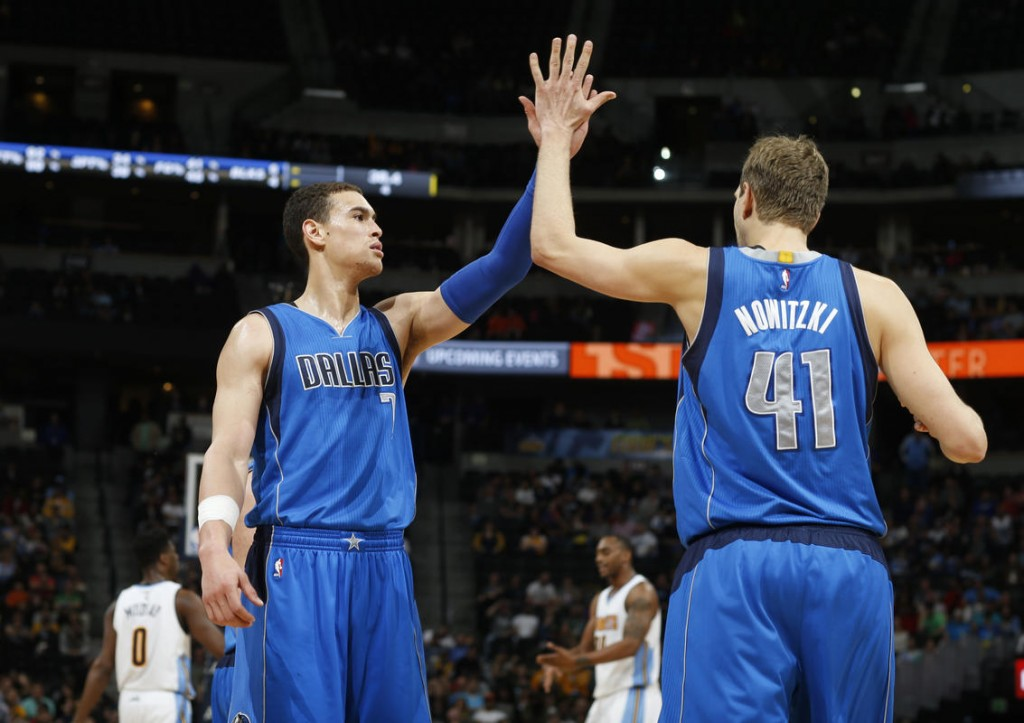 Dallas Mavericks forward Dwight Powell, left, congratulates forward Dirk Nowitzki, of Germany, after forcing the Denver Nuggets to turn over the ball late in the second half of an NBA basketball game, Monday, March 28, 2016, in Denver. The Mavericks won 97-88. (AP Photo/David Zalubowski)
