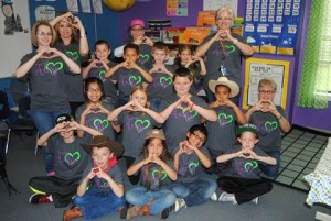 Andy Johnson's second grade class at Aaron Parker Elementary show their love for their teacher who is in critical condition stemming from the flu and pneumonia.  Pictured around the students beginning left are Kristin Hughes, Lisa Rozell, Principal Tammie Bates, Lisa Oliver and Betty Ashby.