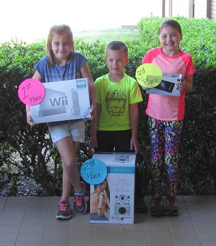 """Higgins Elementary Winners (L to R) 1st place – Mary Grace Gibbons – Wii U with Wii Sports        and Wii Sports Resort 2nd place – Cade Wolfe – Karaoke Singing Machine 3rd place – Myla Geeslin – 7"""" RCA Tablet"""