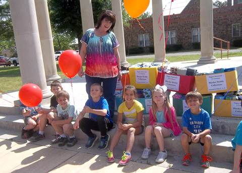One hundred child-sized blankets were carefully packed into boxes by the GT class at Higgins Elementary and donated to the Children's Advocacy Center.  Members sitting on the steps at Bywaters Park from left are Truett Jones (behind balloon), Kaiden Marlowe, Jackson Church, Jaxon Chalupa, Kylen Chennault, Aliyah Hayes, and Eli Allen.  Standing is GT teacher Sonja Carter.