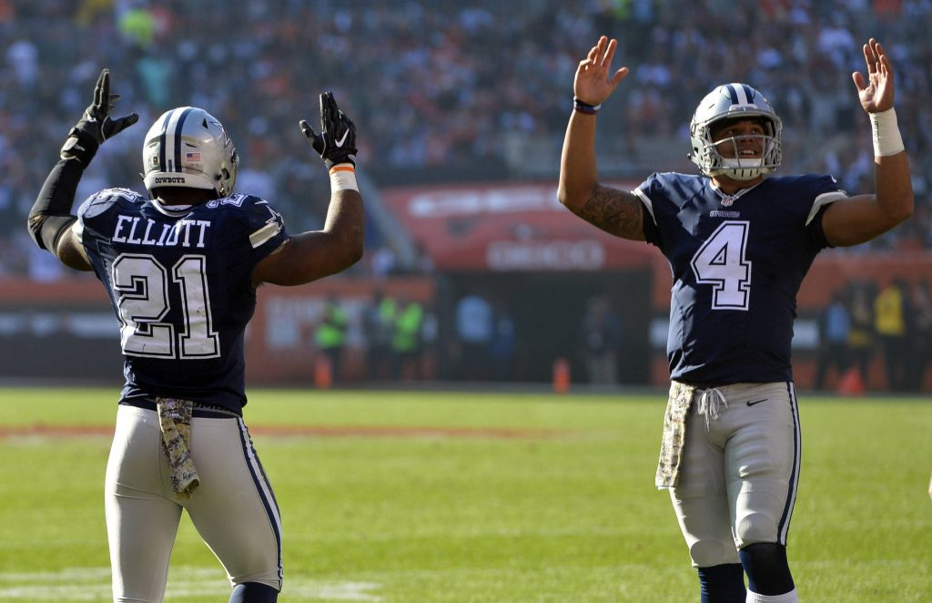 Dallas Cowboys running back Ezekiel Elliott (21) celebrates his touchdown with quarterback Dak Prescott (4) in the first half of an NFL football game against the Cleveland Browns, Sunday, Nov. 6, 2016, in Cleveland. (AP Photo/David Richard)