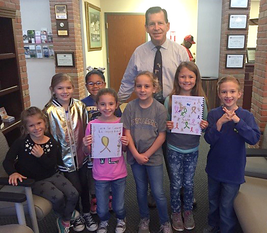 Everett Elementary's Cure for Cancer team presented a book they made to Dr. Ernie Cochran at Texas Oncology. Making the presentation to Cochran from left are Krislyn Bland, Brooklyn Robertson, Aliyah Dangerfield, Izabella Jumper, Lilly Stewart, Adisyn Hedrick, and Noah Langley.
