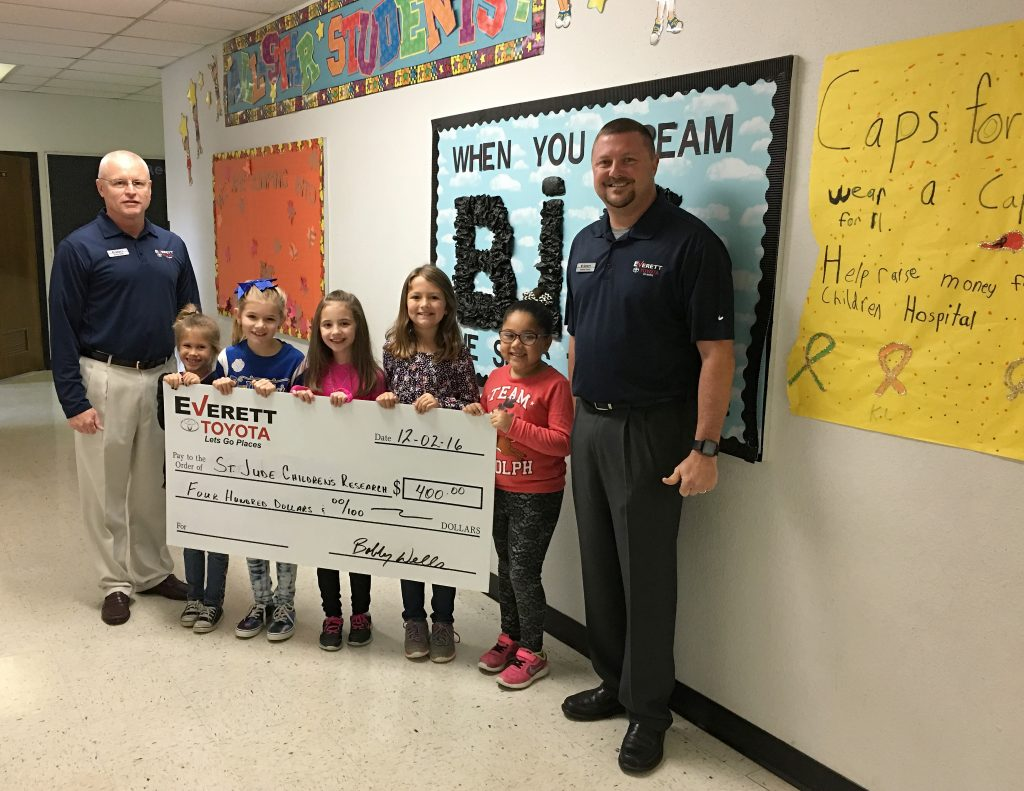 Everett Toyota made a presentation to the Cure for Cancer team at Everett Elementary with a check made out to St. Jude Children's Research Hospital.  Toyota representatives Bobby Wells, left, and Jeremy Prunty, right, stand with students, beginning left, Krislyn Bland, Brooklyn Robertson, Izabella Jumper, Adisyn Hedrick, and Aliyah Dangerfield.  Not pictured are Noah Langley and Lilly Stewart.
