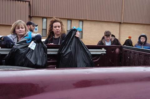 Belinda Peeples and Cassidy Emeyabbi place sacks of wrapped Christmas gifts in the back of a truck.  Gifts and food baskets have been distributed to North Lamar families just in time for Christmas.