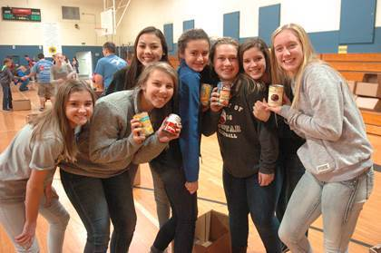 Holding canned goods from the Christmas food boxes are Stone Middle School athletes Makayla Winton, Abby Neilson, Ashley Trenchard, Hannah Gibbons, Emma Doyal, Kendall Stephens, and Hannah Crosswhite.
