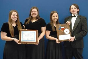 NLHS Band representatives Haleigh Milam, Chloe Whisenhunt, Bailey Swindle, and Ty Rast hold plaques presented by the Association of Texas Small School Bands that will hang in the band hall recognizing the group as being among the best concert bands in the State of Texas.